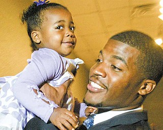 "Brad Smith of the New York Jets, a graduate of Chaney High School, holds his one-year-old niece Kennedy Carpenter of Youngstown during the United Way's ""Champions Among Us"" annual banquet Thursday at Mr. Anthony's in Boardman. Smith and Ohio State junior lineman and Cardinal Mooney High School graduate John Simon spoke at the  event and were honored by organizers as local champions who have represented the Mahoning Valley in a positive manner."