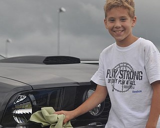 Joseph Paglia poses with his father's car Friday at the Steel Valley Super Nationals at the Quaker City Motorsports Park. The rain prevented racing Friday, the first day of the event.