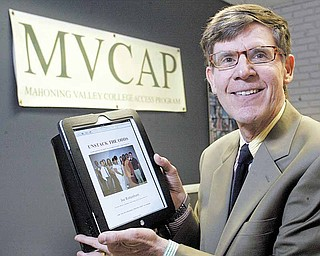 Joe Rottenborn, executive director of Mahoning Valley College Access Program, stands in his offi ce at Kent State University Trumbull Campus holding an iPad displaying a website he has created to help students with getting into and completing college.