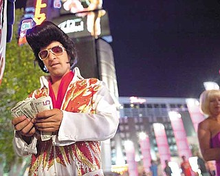 While impersonating Elvis along The Strip, Rodrigo Gonsalez takes a moment to count the night's tip earnings, Thursday, June 23, 2011, in Las Vegas. The number of celebrity impersonators crowding the Las Vegas Strip has grown in recent months, in part because the stalled economy has left many actors and performers in California and Las Vegas without a job.   (AP Photo/Julie Jacobson)