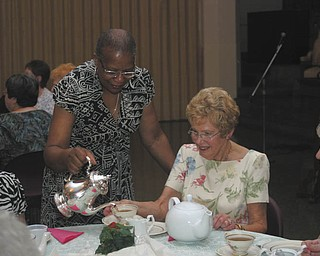 Jackie Burley, executive director of Protestant Family Service, who attended the Trinity UMW's tea, served the other guests at her table. Seated, from left, are Joanie Morrison of Austintown, Marilyn Morelli of Canfield and Elva Easton of Boardman.