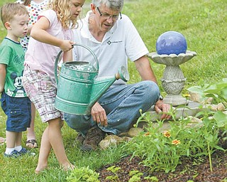 Greg Bowman, executive director of Goodness Grows, a faith-based food and farming ministry at Common Ground Church Community, watches as Julia Gregory, 7, waters plants. Also pictured are Jacob Bacvani, 3,and Leah Bacvani, 7.
