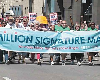Opponents of Senate Bill 5 lead a parade through downtown Columbus to the Secretary of State's Office  on Wednesday to turn in nearly 1.3 million petition signatures seeking to repeal Ohio's controversial collective bargaining law.