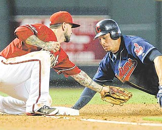 Arizona Diamondbacks' Ryan Roberts, left, tags out Cleveland Indians' Asdrubal Cabrera, as he tries to steal third base during the fourth inning of an interleague baseball game Wednesday, June 29, 2011, in Phoenix. (AP Photo/Ross D. Franklin)