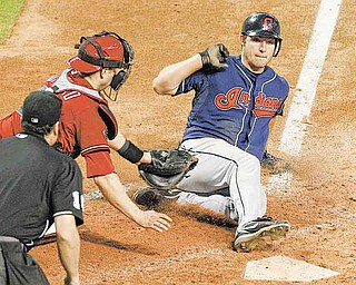 Cleveland Indians' Lou Marson, right, scores ahead of the tag by Arizona Diamondbacks' Miguel Montero as umpire Mike DiMuro, left, looks on during the ninth inning in an interleague baseball game Wednesday, June 29, 2011, in Phoenix. (AP Photo/Ross D. Franklin)