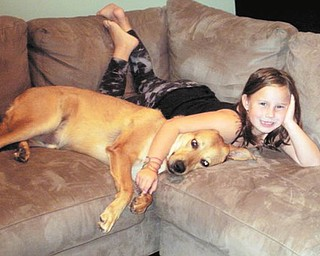 Madalyn Smith of Boardman cuddles with her dog, Bullseye, who was adopted as a puppy from Mahoning County Dog Pound.