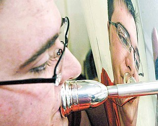 Tuba player Stephen Orlando is reflected in his horn as he rehearses with Girard Community Band. The band includes musicians of various ages and stages in their musical careers.
