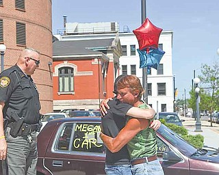 Frank Fordley hugs Richard McGrath's, a Trumbull County Sheriff's deputy, daughter, Megan, 16, outside the Trumbull County Sheriff's Office on High Street in Warren as Richard McGrath looks at the car, a 1992 Dodge Spirit. Fordley runs a music store and car lot on Mahoning Avenue in Champion.