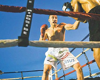 """Campbell's Jake Giuriceo backs Georgia's Winston Mathis into the corner during their six-round light welterweight bout at Friday's """"Real Deal"""" boxing show at the Covelli Centre."""