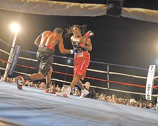 Dannie Williams, right, follows through on a right hook as his opponent, Oscar Cuero, tries to land a right uppercut during Friday's 10-round lightweight bout outside the Covelli Centre.