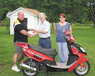 Fun in their future? Kiwanis Club of Western Mahoning County raffled off a street-legal scooter on June 22. Above is the winner of that raffle, Ken Frost, left, who took possession June 24. In the center is Dave Pinney, and at right is Frost's wife, Holly.