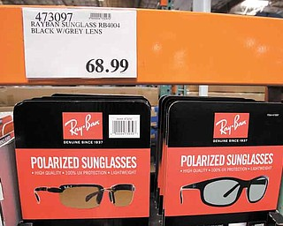 In this June 13, 2011 photo, RayBan sunglasses are displayed at Costco in Mountain View, Calif. Shoppers go into Costco, TJ Maxx or a DSW shoe store looking for a bargain on something they need and end up splurging on irresistible finds.(AP Photo/Paul Sakuma)