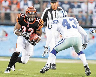 Cincinnati Bengals running back Cedric Benson (32) runs against Dallas Cowboys safety Gerald Sensabaugh (43) in the first quarter of the Hall of Fame NFL football game Sunday, Aug. 8, 2010, in Canton, Ohio. (AP Photo/Mark Duncan)