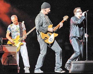 U2 members Adam Clayton, left, The Edge and Bono perform in Miami on June 29. The band's stadium tour comes to Pittsburgh's Heinz Field on July 26.