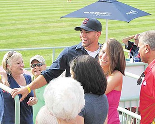 Marine Sgt. Frank Pezzano (in Indians cap) greets family and friends who threw him a surprise homecoming party Friday night at the Scrappers game. At right are his girlfriend, Stephanie Cole, and his father, Frank Pezzano. At left is the sergeant's mother, Jen.