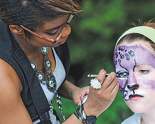 RAMI DAUD   THE VINDICATOR.Alpha Psi Omega Sorority member Brittney Grant paints the face of Kelly Sullivan also of Alpha Psi Omega at a booth at theYSU ArtistsÕ Marketplace outside of the Kilcawley Center Saturday afternoon.
