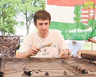 """Andrew Check, 18, of Youngstown plays the cimbalom, a Hungarian instrument, during YSU's Summer Festival of the Arts. Check played the song """"Priest Pipe"""" on Sunday as others sang along during the final day of the event."""