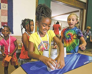 Savannah Kitchen, 6, of Youngstown gets a reaction from Christine Innocenzi, 9, right, as she fumbles a cup while practicing speed stacking after a demonstration Tuesday by Andy Innocenzi, a member of Team USA sport stackers. Other campers watch. Andy's siblings assisted at the program and also include Laura, 16, and Anthony, 11.