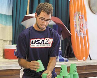 Andy Innocenzi of Cortland, a member of Team USA cup stackers, demonstrates the speed of sport stacking to participants in this week's summer day camp at Martin Luther Lutheran Church in Youngstown. Innocenzi, 19, has seven Ohio records in his age division and one national record.