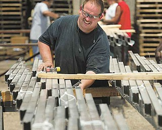 John Cheeks of Niles prepares a load of solar flex rack frames for shipping at Northern States Metals Co., located on the Youngstown's West Side.