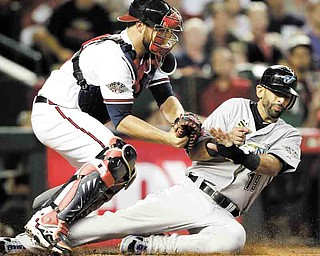 American League's Jose Bautista of the Toronto Blue Jays is tagged out at home plate by National League's Brian McCann of the Atlanta Braves after trying to score on a hit by American League's Adrian Beltre of the Texas Rangers during the fourth inning of the MLB All-Star baseball game Tuesday, July 12, 2011, in Phoenix. (AP Photo/David J. Phillip)