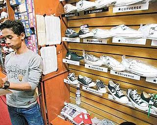 In this photo taken July 12, 2011, a shop attendant stands near Converse shoes on display at a store in Jakarta, Indonesia. Workers making Converse sneakers in Indonesia said supervisors throw shoes at them, slap them in the face and call them dogs and pigs. Nike, the brand's owner, admits that such abuses have occurred among the contractors that make its hip high-tops but claims there was little it could do to stop it. (AP Photo/Irwin Fedriansyah)