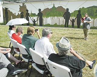 Artist Briar Rantilla of Warren speaks during a dedication ceremony for a mural of downtown Warren that he created on a building at 310 Elm Road NE in Warren.
