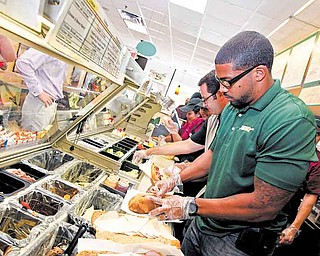 Houston football star Arian Foster prepares BBQ Pulled Pork sandwiches for fans at a Subway restaurant at the Subway All-Star BBQ in Los Angeles. Subway is one of several fast-food restaurants updating its look.