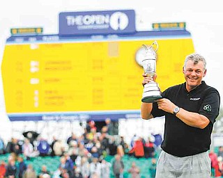Northern Ireland's Darren Clarke holds the Claret Jug trophy in front of the scoreboard on the 18th green as he celebrates winning the British Open Golf Championship at Royal St George's golf course Sandwich, England, Sunday, July 17, 2011. (AP Photo/Peter Morrison)