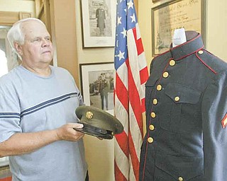 William d Lewis the Vindicator  Ken Miller Trusteeof the Girard Historical Society, shows a Marine uniform on display at the Barnhisel House in Girard as part of military uniform exhibit.7-18-11.