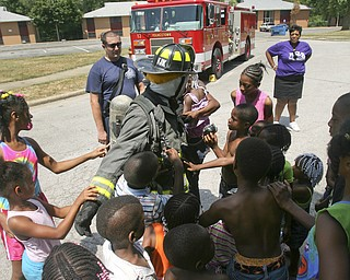 JESSICA M. KANALAS | THE VINDICATOR..Firefighter Shaun Rosan from Engine 12 dresses up in his uniform and lets the kids touch him and talk to him. The firemen came out to teach the kids not to be afraid of the fire trucks and emergency personnel they see on a daily basis. ..-30-