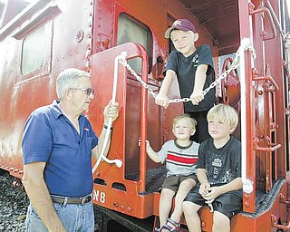 Jack Crouse, owner of Crouse Mills True Value in North Lima, stands with his grandsons, clockwise from top, J.D., Heath and Carson, standing on an old railroad car at his store. Crouse serves on the committee for the Beaver Township bicentennial celebration that begins Tuesday.