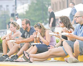 From left, Erin Simione of Boardman and Struthers residents Dan Monico, Jamie Rivello and Bridget and Bill Bowes take a break Saturday evening to enjoy chicken wings at the Greater Youngstown Wing Fest outside Covelli Centre.