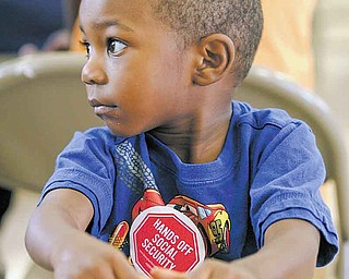 """Two-year-old Jordan Jackson of Youngstown wears his """"Hands off Social Security"""" sticker as he waits for Sunday's town-hall meeting at the Union Baptist Church in Youngstown to begin. The meeting discussed the impact of possible cuts to Social Security, Medicare and Medicaid."""