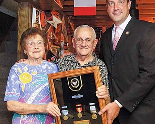 Korean War veteran Donald Lariccia stands in his Austintown home with his wife, Mary, and receives his service medals from U.S. Rep. Tim Ryan.