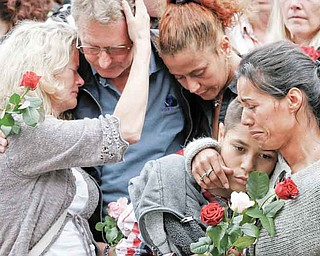 """People comfort each other outside Oslo City Hall as they participate in a """"rose march"""" in memory of the victims of Friday's bomb attack and shooting massacre Monday July 25, 2011. Anders Behring Breivik has admitted bombing Norway's capital and opening fire on a political youth group retreat, but he entered a plea of not guilty, saying he wanted to save Europe from Muslim immigration. Police announced Monday that they had dramatically overcounted the number of people slain in a shooting spree at a political youth group's island retreat and were lowering the confirmed death toll from 86 to 68. (AP Photo/Erlend Aas, Scanpix Norway)"""