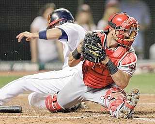 Los Angeles Angels catcher Jeff Mathis catches the throw to force the Cleveland Indians' Orlando Cabrera out at the plate in the ninth inning of Monday's baseball game in Cleveland. One batter later, Jason Kipnis drove in the winning run for the Tribe with his fi rst major league hit. The final score was Cleveland 3, Los Angeles 2.