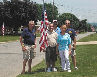 """Flags fly for fundraising: Struthers Rotary Club has begun its """"Fly the Flag"""" project. The Rotary places an American flag in your yard the weeks of Memorial Day, Flag Day, Independence Day, Labor Day and Veterans Day for a yearly fee of $25 and picks it up after the holiday. Proceeds will be used to support local youth, community and international Rotary projects. From left to right, Rotarians Dan Becker, Bryan Higgins, Tom Baringer, Marge Diorio and Mike Krake have just finished placing one of five flags on a street in Struthers."""