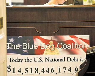 A staff member sits at a reception desk behind a national debt poster in the office of Rep. Jim Cooper, D-Tenn., Tuesday, July 26, 2011, in the Longworth House Office Building on Capitol Hill in Washington. (AP Photo/Harry Hamburg).