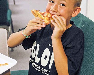 Blase Schuller, 6, of Champion, enjoys his lunch Tuesday at the church, which offered pizza for lunch.