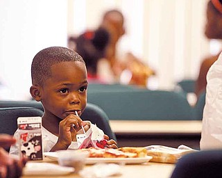 Four-year-old Kenny Byrd drinks the milk offered with his lunch Tuesday at the program in Warren. An average of 50 children age 1 to 18 attend the meal each day. It is one of several such programs that operate in the Mahoning Valley in the summer.