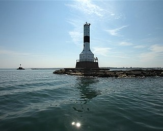 In this photo taken Wednesday, July 20, 2011, the lighthouse standing at the entrance to Conneaut Harbor is shown in Conneaut, Ohio. The Coast Guard conducted a tour for interested parties in preparation for the auctioning of the property. (AP Photo/The Plain Dealer, Thomas Ondrey)