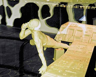 This undated photo provided by the American Dairy Association shows a butter sculpture display at the Ohio State Fair in Columbus, Ohio. The fair revealed on Tuesday, July 26, 2011, that the usual cow and calf made of butter are accompanied this time by a butter space shuttle and astronaut. (AP Photo/American Dairy Association)