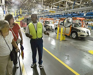 General Motors Co. Lordstown worker Todd Burns shows Irma Locke, left, and her daughter Nancy Locke, of North Jackson, the assembly line during GM's open house Thursday. The 9,000 who toured went on 30-minute tours through the east and west complexes.