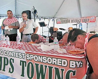 Duke Girardi of Boardman, far left, stands up as he finishes eating around a pound of rigatoni at the Greater Youngstown Italian Fest on Saturday afternoon. Girardi finished first in the pasta-eating contest, which he has entered in each of the last 11 years. The emcee, second from left, was Todd DeMain, and the other contestants are, seated from left, Michael DeLucia III of Green near Akron, MichaelDeLucia II of Green and Scott Cross of Columbiana.