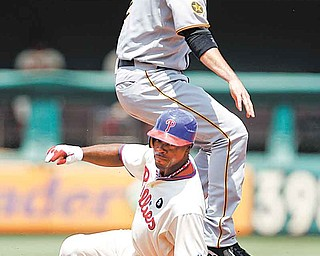 Pittsburgh Pirates shortstop Brandon Wood, top, leaps to avoid Philadelphia Phillies' Jimmy Rollins after forcing him out at second base on a fielder's choice by Shane Victorino in the fi rst inning of a baseball game Sunday in Philadelphia. Victorino was safe at fi rst. The Phillies won 6-5 in 10 innings.