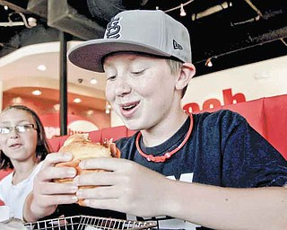 This is so good - it's thicker than most burgers, says Jeremy Hofman, 13, of O'Fallon, critiquing his first bite of his BBQ, Bacon and Cheddar Burger, his first ever burger, at Smashburger in St. Charles, Missouri, July 26, 2011. The better burger movement is sweeping through St. Louis. The latest addition is Smashburger, one of the fastest-growing chains out there, which opened its first St. Louis metro area location. His younger sister Amanda, 9, is on the left. (Laurie Skrivan/St. Louis Post-Dispatch/MCT)