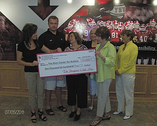 Dr. Melinda Wolford, left, and her husband, Eric Wolford, Youngstown State University head football coach, present a check for $1,600 to officials of the Rich Center for Autism, including, right from center,  Phyllis Ricchiuti, board president; Georgia Backus, director; Geri Kosar, founding member; and Juli Costas, board member. The funds were raised through the second annual Women's Football Clinic at YSU's Stadium Club in May, organized by Dr. Wolford, Dan Kopp, Coach Carmen Bricillo and Lynn Cadle. The event aims to inform local women about the game while raising funds for area charities. It included dinner, a tour of Stambaugh Stadium and demonstrations by coaches on game strategies and regulations.  Last year's proceeds went to breast-cancer research, but the coaches wanted the funds to stay in the YSU community this year, so they chose the Rich Center, which has operated on the campus since 1995 and currently serves 70 families.
