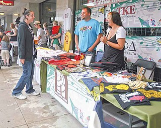Kate Butler, 27, right and friend Mark Griffin, 28, sell Rusty Waters T-shirts during the Vex Fest on Sunday. Butler, a Youngstown native, cofounded the company in 2005 promoting the grit of Rust Belt cities.
