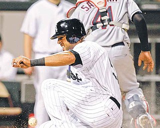 The Chicago White Sox's Alex Rios scores on a single hit by Tyler Flowers during the fourth inning of their baseball game against the Cleveland Indians in Chicago, Thursday, Aug. 18, 2011. (AP Photo/Nam Y. Huh)